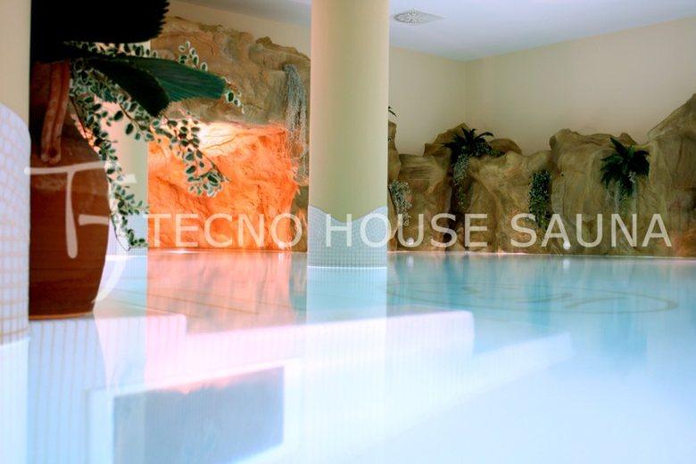 Centro benessere con grotta emozionale su piscina, parete rocciosa e cascate artificiali