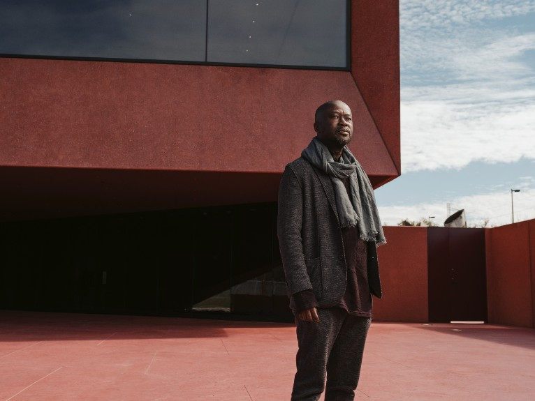 David Adjaye in front of a building he designed.